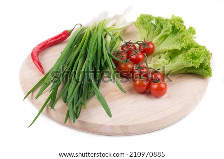 Onions and cherry tomatoes on a wooden board. #210970885
