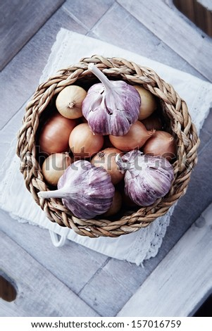 Onions and garlic bulbs in a rustic basket #157016759
