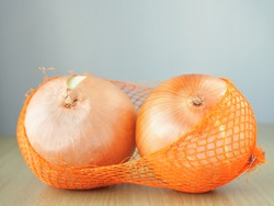 Onions in orange mesh bag are placed on wooden table with copy space, Plants with pungent smell and medicinal properties.