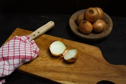 onions sliced on cutting board with knive and kitchen towel for cooking preparation in dark mood