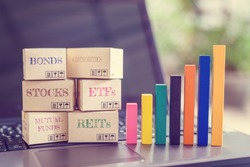 Online asset investment / portfolio diversification management for long-term profit growth concept : Boxes of financial products e.g bonds, commodities, stocks, mutual funds, ETFs, REITs on a laptop