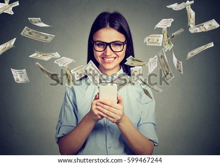 Online banking money transfer, e-commerce concept. Happy young woman in glasses using smartphone with dollar bills flying away from screen isolated on gray wall background.