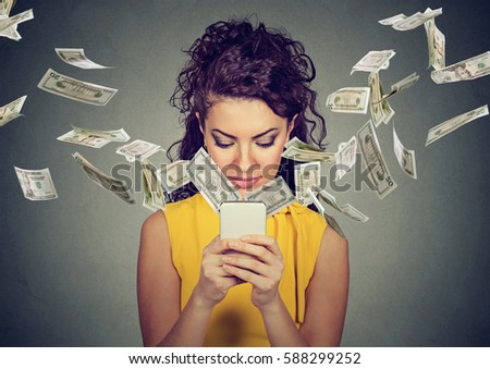 Online banking money transfer, e-commerce concept. Happy young woman using smartphone with dollar bills flying away from screen isolated on gray wall background.