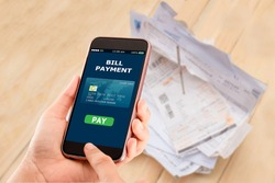 Online bill payment concept.Hands holding mobile phone on blurred Electric bill as background