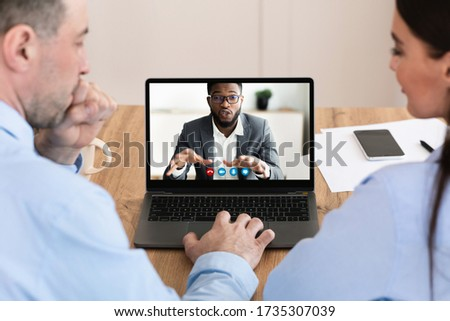 Online Business Concept. Back view of two colleagues having virtual negotiation with their male coworker, copy space