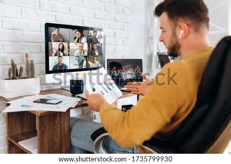 Online business meeting. A young business man communicates by video conference with his business team about a work strategy and plan. Work from home