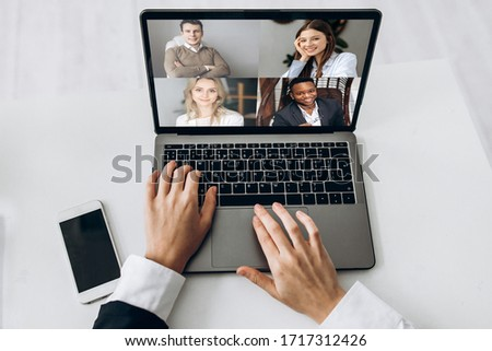 Online business meeting. Business team working from home in a video conference. The girl communicates via video call communication using laptop with her business colleagues about the future strategy