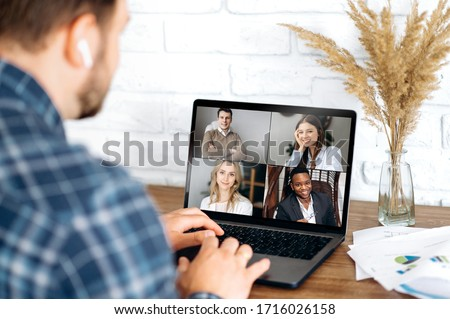 Online business meeting in video conference in the zoom app. A young attractive guy communicates with his colleagues on a video call using a laptop. Distant work at home