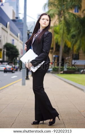 Online Business Mobility Concept With A Full Body Portrait Of A Young Business Woman In Black Suit On The Move Around Town With A Laptop In Hand