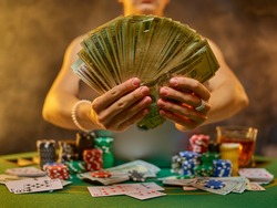 Online casino. Gambling. The woman at the gambling table is holding a large amount of money in her hands. Playing cards and chips are laid out on the playing table. A chance for luck and victory.