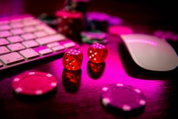 Online casino. Online poker. On the table there are game pieces and dice next to the keyboard. Game chips for betting in gambling. Dice. Poker chips.