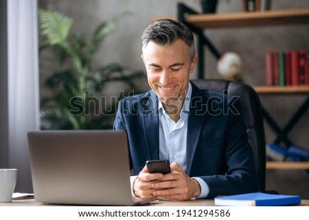 Online chat. A cheerful, handsome caucasian businessman is sitting at his desk, using a mobile phone while working, browsing the Internet, answering email, and texting with a friend or family, smiling Photo stock ©