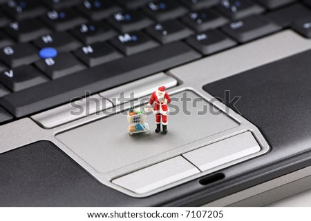 Online Christmas shopping concept. Miniature Santa Claus standing on a laptop pushing a shopping cart.