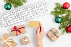 Online christmas shopping concept with gift boxes, keyboard and mockup of golden credit card. Top view, flat lay, mock up
