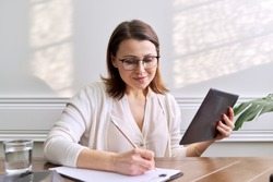 Online communication, consultation, training, business. Woman teacher, mentor, psychologist looking at webcam of tablet, talking, counseling, taking notes on paper. Technology distance lifestyle