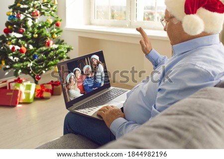 Online communication in quarantine and staying in touch with relatives. Grandfather in Santa hat sitting on sofa at home on Christmas Day, video calling family and waving hand happy to see grandkids