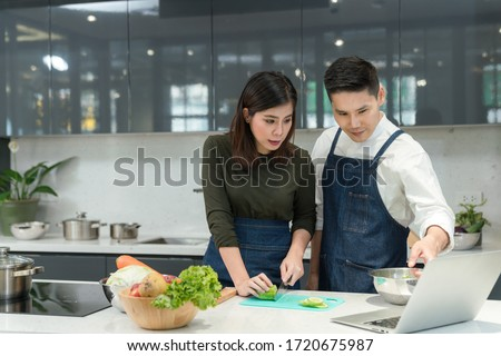 Online cooking class with computer. Asian Couple cooking together in home kitchen. Female slice vegetables and cooking with laptop. Young couples are helping to chop vegetables in the kitchen.