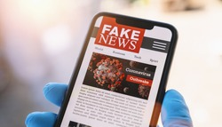 Online Corona Fake news on a mobile phone. Close up, man reading Fake news or articles about covid-19 in a smartphone screen application. Hand with gloves holding smart device. COVID19 nCov Outbreak.