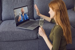 Online date dating. A young woman is in a living room with a laptop. On the laptop screen a handsome young man with a glass of wine.