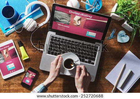 Online dating website on a laptop display, hardwood desktop and stationery on background #252720688