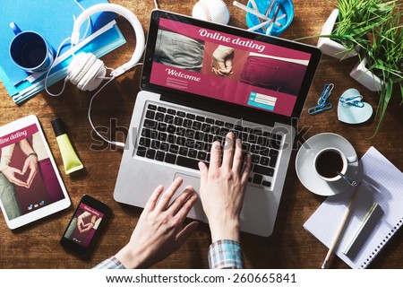 Online dating website on a laptop display, hardwood desktop and stationery on background #260665841