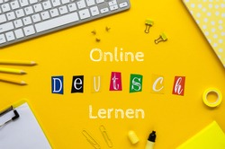 ONLINE DEUTSCH LERNEN sign on a student table framed withoffice stationery and pc keyboard. Top view on a yellow background