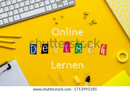 ONLINE DEUTSCH LERNEN sign on a student table framed withoffice stationery and pc keyboard. Top view on a yellow background Stock foto ©