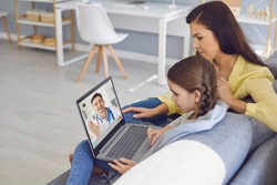 Online doctor. A male doctor online consults a diagnosis of symptoms to a mother and daughter through video chat using a laptop.