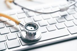 Online doctor concept with stethoscope on keyboard.