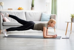 Online domestic sports concept. Mature woman exercising to video on laptop, doing elbow plank at home. Side view of senior lady working out, keeping her body fit during covid-19 isolation