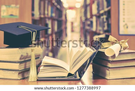 Online E-learning class and internet education success with e-book computer laptop, graduation hat, academic cap, mortarboard and degree certificate on books in class or library study room