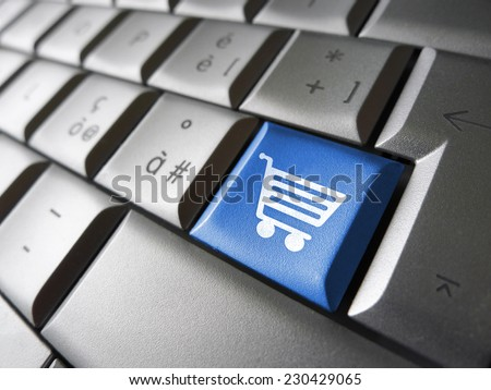 Online e-shopping concept with basket icon and symbol on a blue laptop computer key for Internet website and on line business.