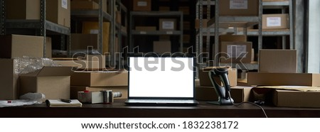 Online ecommerce store mockup, dropshipping business website concept. Table with laptop computer mock up blank white screen, shipping boxes, retail marketplace, warehouse delivery background, banner. Stockfoto ©