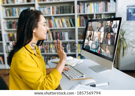 Online education. A female student learning online at home, she waving hand to other students or colleagues on computer monitor in video conference and smiling