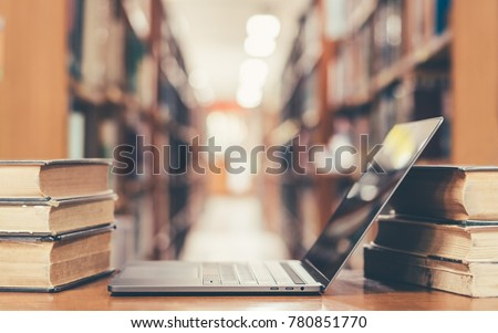 Online education course, E-learning class and e-book digital technology concept with pc computer notebook open in blur school library or classroom background among old stacks of book, textbook archive