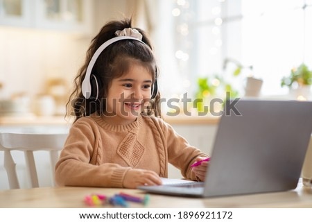 Online Education. Cute little Girl Study At Home With Laptop And Wireless Headphones, Adorable Kid Having Web Lesson With Teacher, Enjoying Distance Learning During Quarantine Time, Free Space