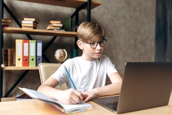 Online education. Distance learning. A clever schoolboy with glasses sits at home at a table and learning online using a laptop and concentrated writes information in her notebook