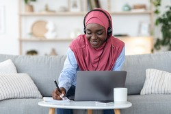 Online Education For Muslim Women. Happy Black Islamic Lady In Hijab Studying With Laptop And Headset At Home, Taking Notes, Watching Webinar In Internet, Enjoying Distance Learning, Copy Space