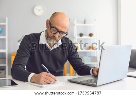 Online education. Mature man with a gray beard in teaches learning a university lecture online video call at home.