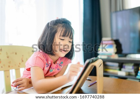 Online education, Online learning.Little asian girl studying homework math during her online lesson at home with tablet, Social distance, Quarantine, self isolation, Online education concept.Covid-19.