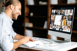 Online education. Smart caucasian guy gains knowledge watching lesson online. Young man takes notes during webinar, listening lecture on video call. Female teacher and students on a screen