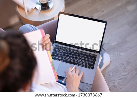 Online education. The girl is sitting in a chair with a laptop and notebook engaged with the teacher online. Online lessons. Online language lessons.