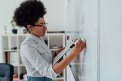 Online english course. Side view of a young afro american female teacher writing on a whiteboard while teaching English language via internet from home. Focus on hand. E-learning. Stay home. COVID-19
