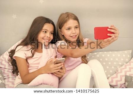 Online entertainment. Explore social network. Smartphone for entertainment. Kids taking selfie. Smartphone application concept. Girlish leisure pajama party. Girls smartphone little bloggers.