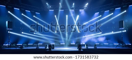 Photo of  Online event entertainment concept. Background for online concert. Blue stage spotlights. Empty stage with blue spotlights. Blue stage lights. Online COVID-19 concert. Live streaming concert