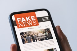 Online fake news on a mobile phone. Close up of woman reading Fake news HOAX or articles in a smartphone screen application. Hand holding smart device. Mockup website. Fake Newspaper portal.