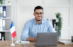 Online foreign languages tutoring. Cheerful Arab male teacher giving French class, communicating on laptop from home. Experienced college professor giving new material to students on web