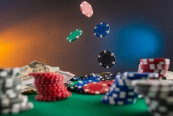 Online gaming business, casino, poker. Flying, levitating chips against the background of a poker table, money and chips. Creative light. Background for the casino gaming business.
