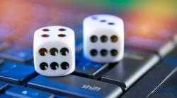 Online gaming platform, casino and gambling business. Bones on laptop keyboard.