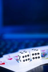 Online gaming platform, casino and gambling business. Cards, dice and multi-colored game pieces on laptop keyboard.